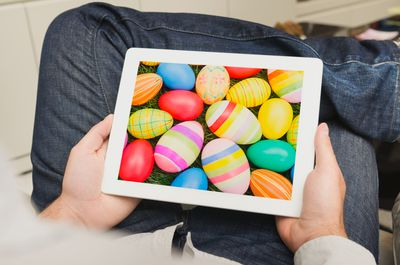 Person holding a tablet with a free Easter egg wallpaper