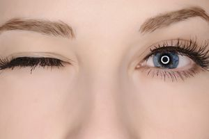 Eye color closeup of blue eye one eye winking