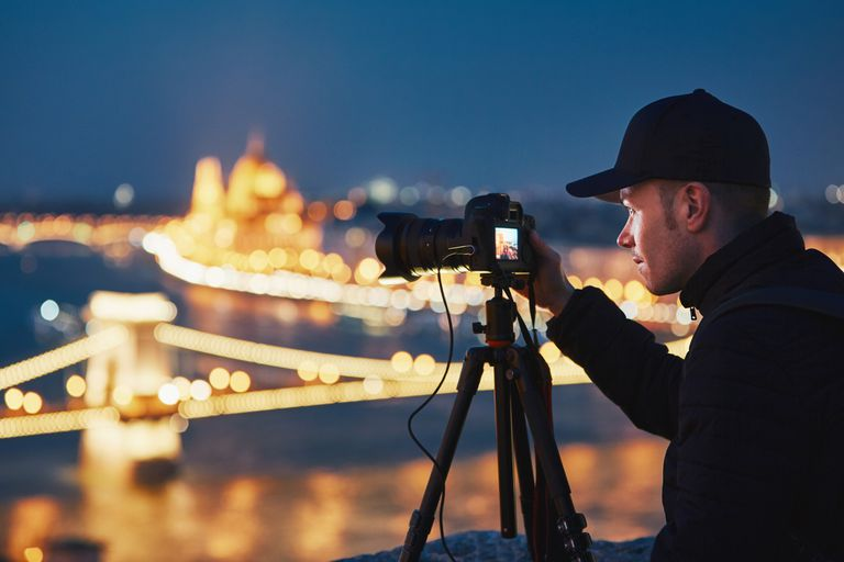 A photographer setting up a night shot of city lights.