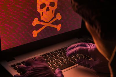 An images of a hacker working on a laptop.