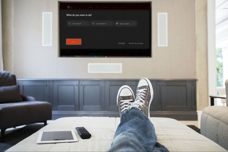 TV mounted on wall with person's feet up on sectional