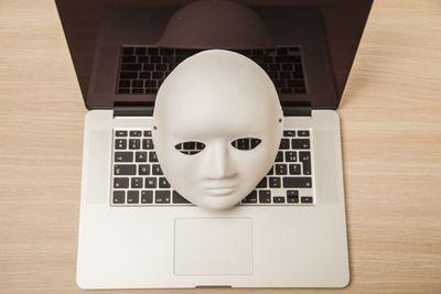 A mask sitting on a laptop.