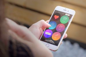 A hand holding an iPhone that's using the Listen Gesture Music Player app