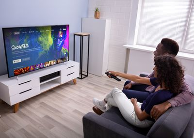 A man and woman sitting on a couch watching Hulu on their TV.
