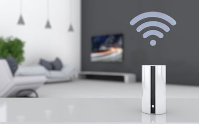 A smart home speaker with a television in the background.