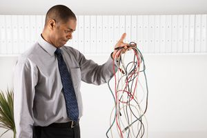 Businessperson examining a tangle of electronic cords