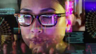 A woman looking at a screen, with its image reflected in her glasses