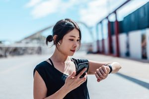 A woman standing outside looking at her smartwatch and smartphone