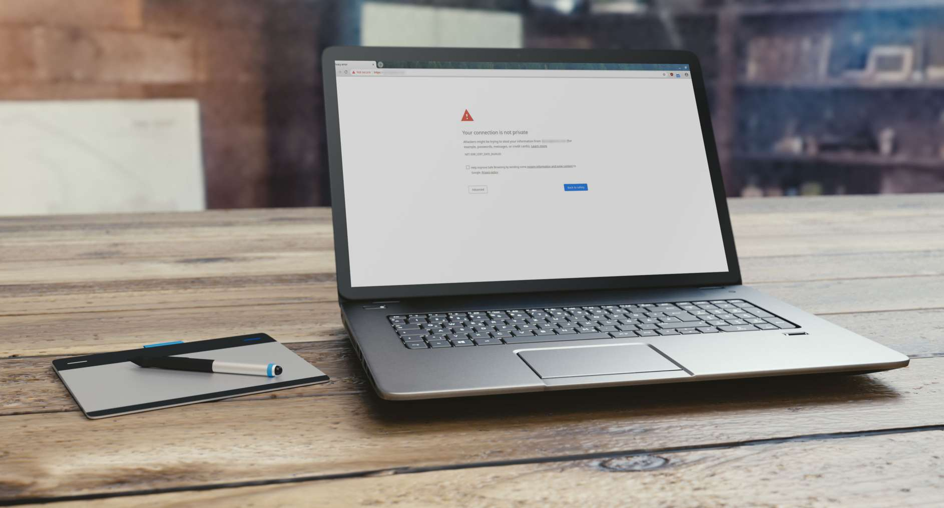 PC laptop on wooden table with Chrome privacy error onscreen