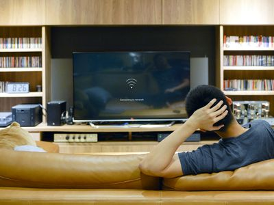 A man sitting on a brown leather couch watching his TV and waiting for his Amazon Fire TV Stick to stop buffering.