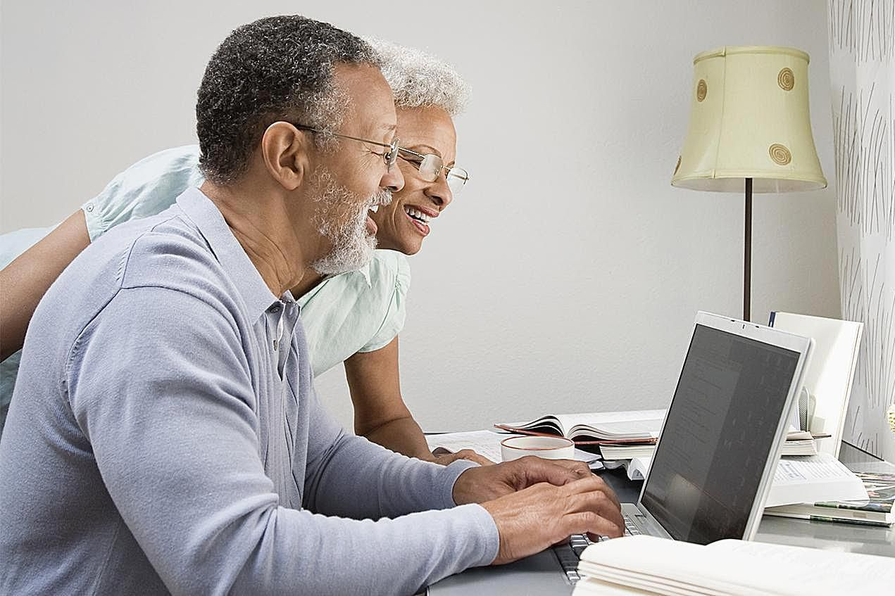Couple in their home office looking at a laptop.