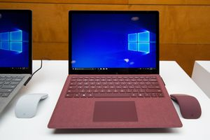 A photo of a red Windows 10 Surface laptop with its touchpad in full view and its screen turned on.