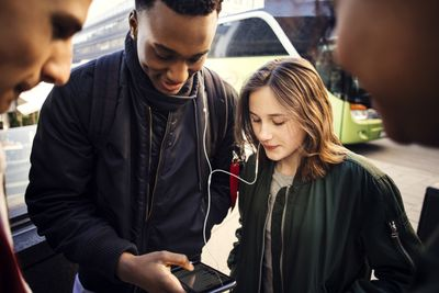 Teenage girl and boy listening music from smart phone while showing to friends in city
