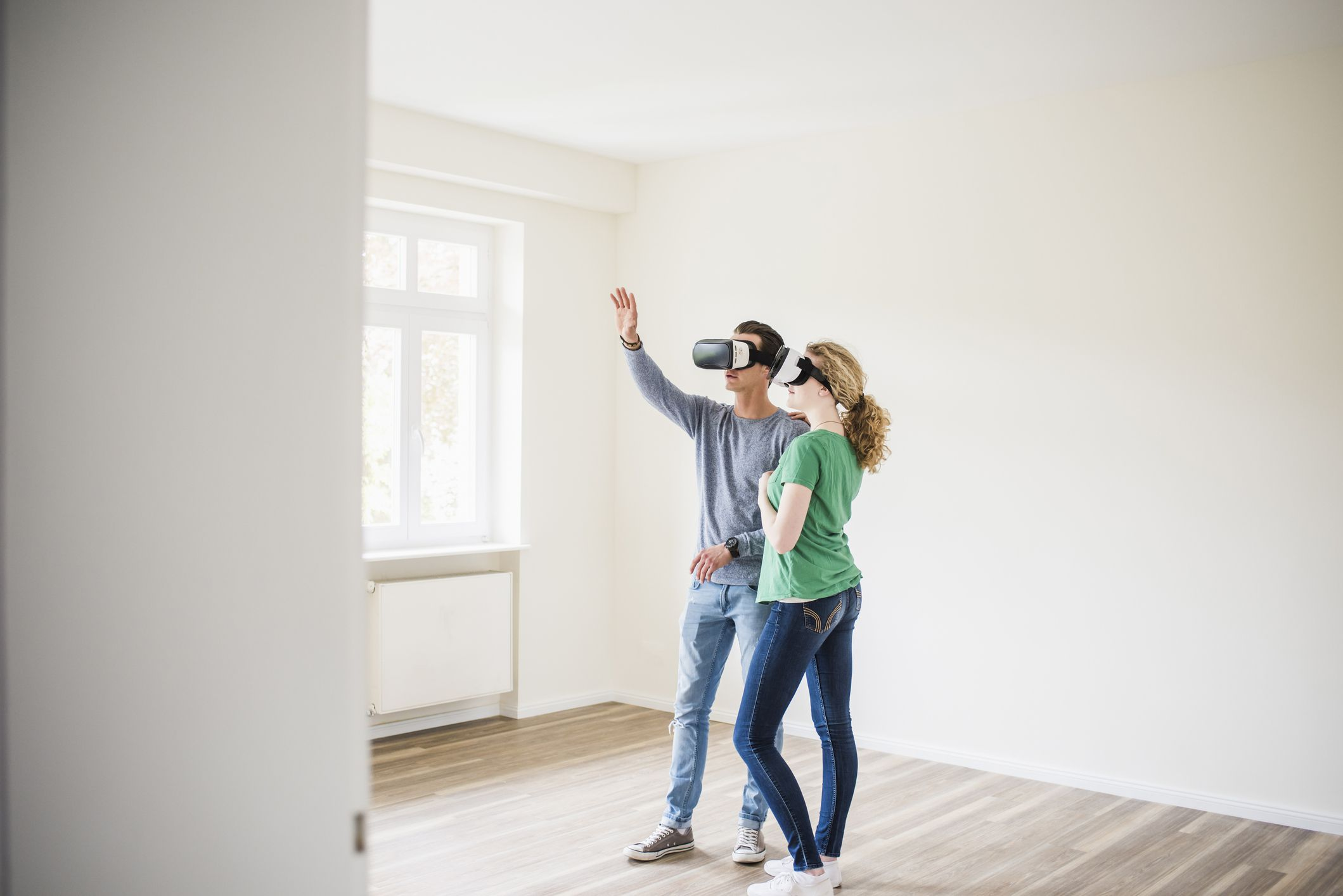 A couple standing in an empty apartment wearing VR glasses.