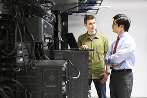 Business owner talking to tech support with laptop next to servers