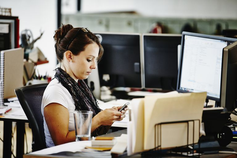 Businesswoman in office working on smartphone