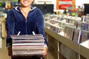 A woman holding a stack of vinyl records while standing inside a music store.