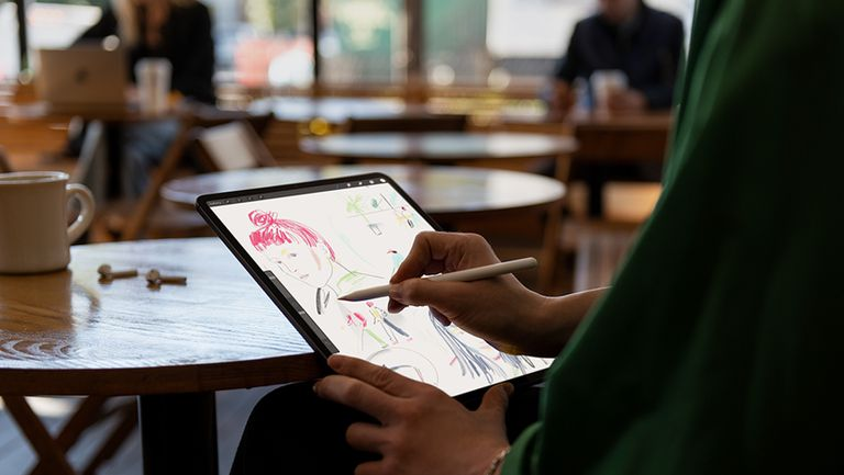A man sketching on an iPad Pro using an Apple Pencil
