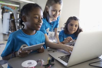 Girls programming electronics at laptop and digital tablet in classroom