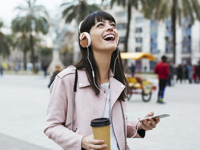 A vacationer laughing and listening to music on a smartphone