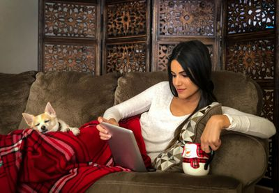 A woman lounging on the couch streaming TV on a tablet.