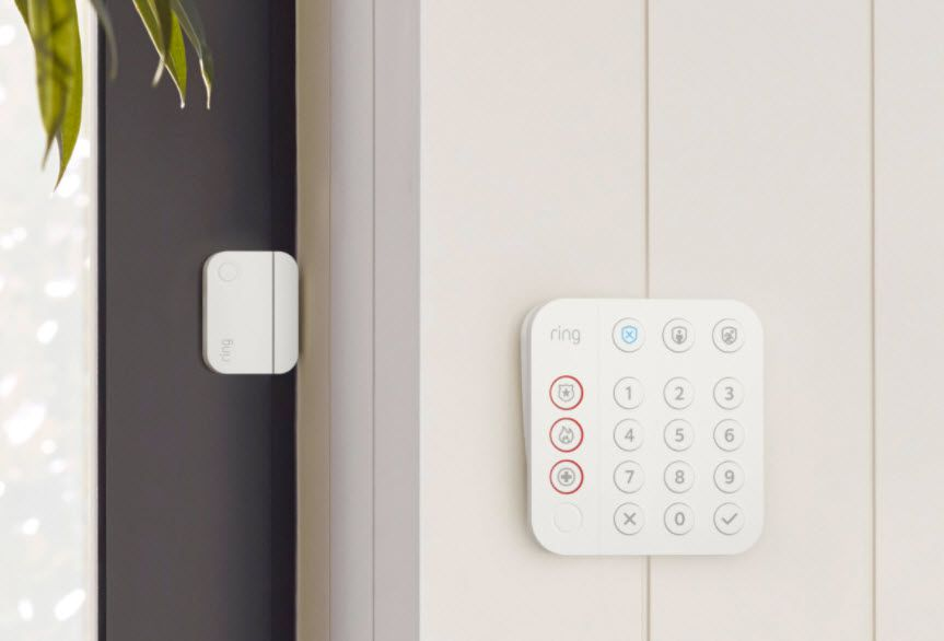 A closeup of a Ring alarm system keypad and door sensor.
