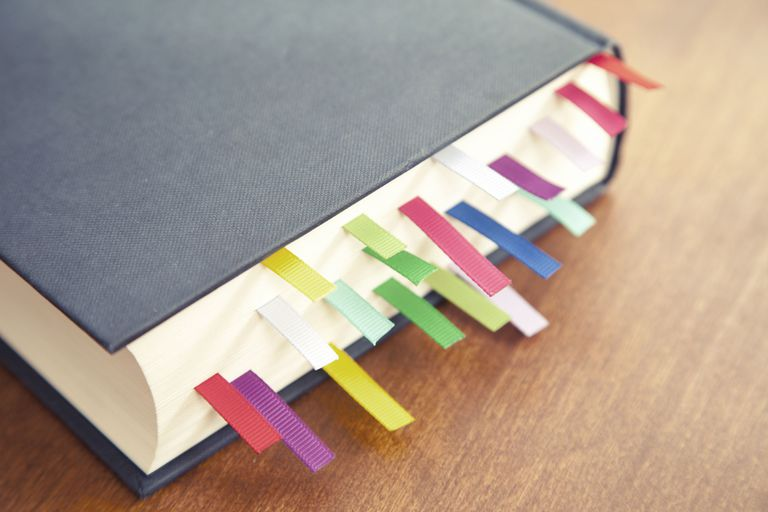 Book with a lot of different colored bookmarks