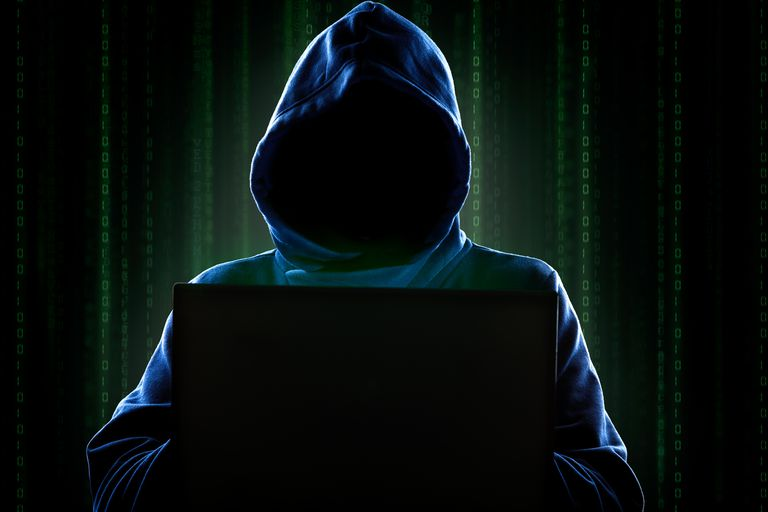 Hooded figure behind a computer.