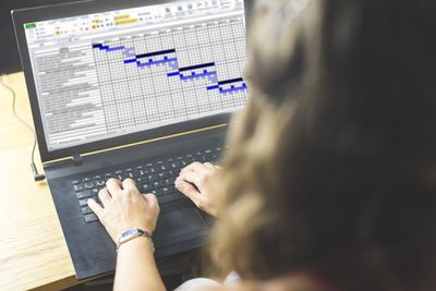 Woman typing on a computer with a spreadsheet on the screen