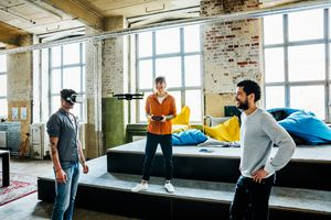 A group of young adults using a drone and a VR headset inside someone's loft apartment.