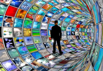 A man standing in a computer generated tunnel of numerous TV shows and movies.