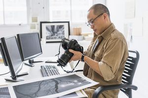 Photographer looking at photos stored on camera in studio