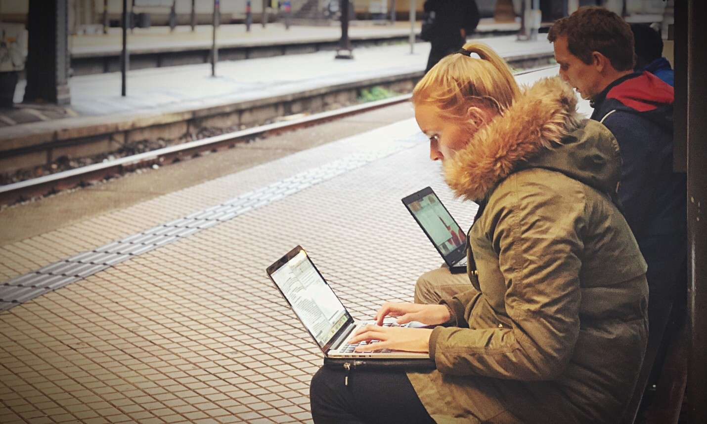 People waiting in a train station using laptop computers.