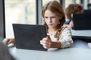Student reading on tablet at school