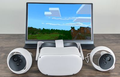 An Oculus Quest 2 and controllers, with Minecraft VR mirrored on a display.