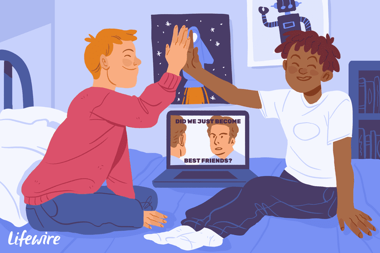 Two best friend shigh-fiving on a bed in front of a laptop with