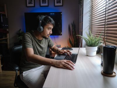 A man wearing headphones sitting at a desk with a laptop in front of him