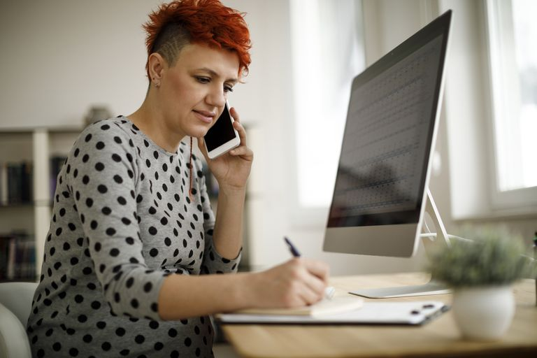 A woman on the phone in front of a computer, writing on a notepad