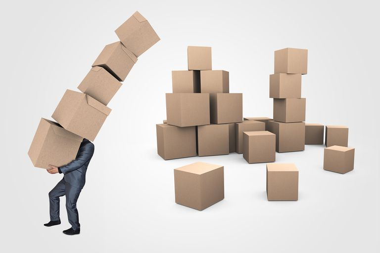 Business owner carrying a large stack of boxes with a larger pile of boxes behind him.