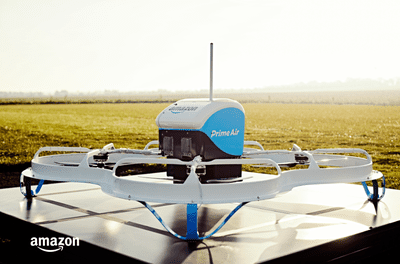 Amazon Prime Air delivery drone on landing pad in a field.