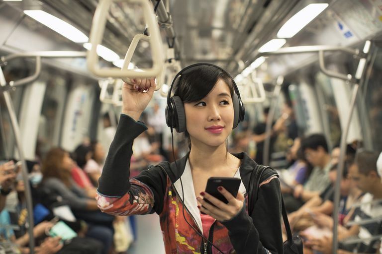 Young woman listening to music while commuting.