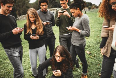 Group of teenagers standing around, looking at their phones
