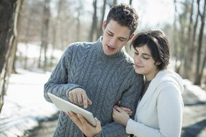 Couple looks at computer tablet while standing close on winter day in woods.