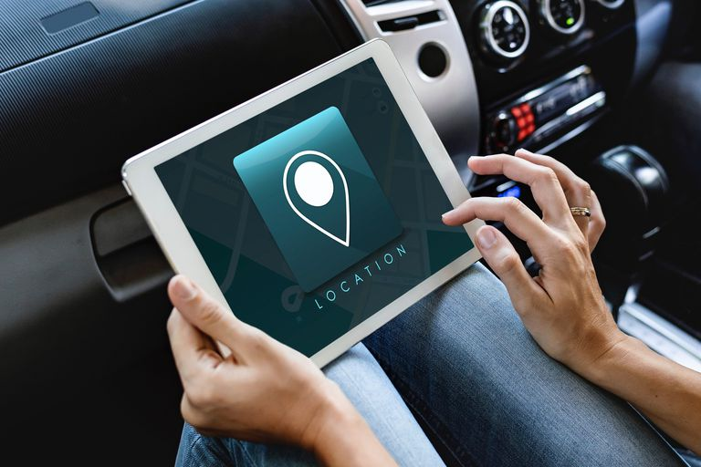 Stock photo of a person sitting in a car with a tablet using a generic GPS location app.