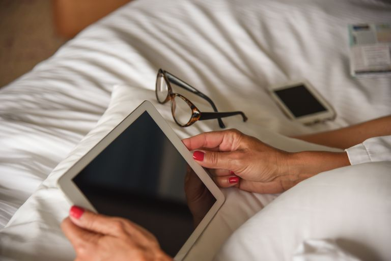 Woman Using Digital Tablet On Bed