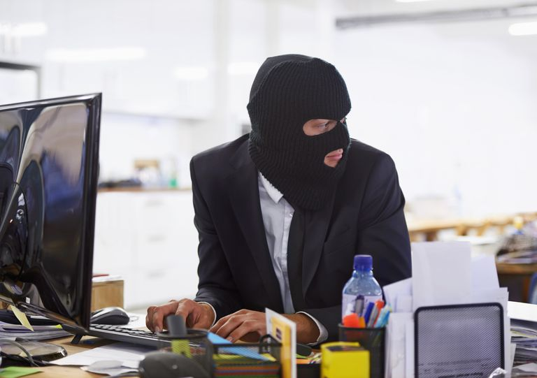 Person at computer in ski mask and suit
