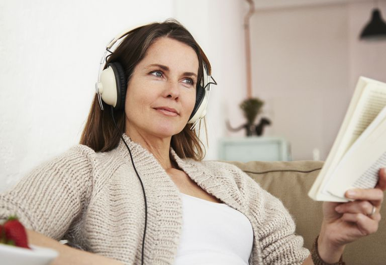 Middle-aged woman sitting on sofa, listening to music and reading book