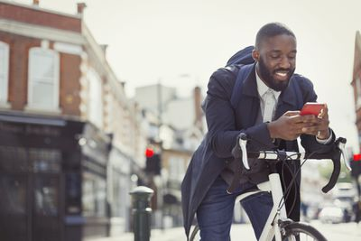 Businessperson on a bicycle, emailing with a cellphone