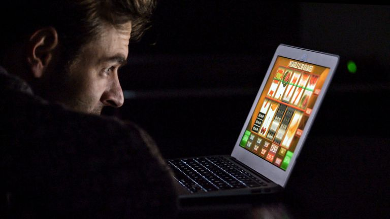 A man playing a slot machine game on a laptop