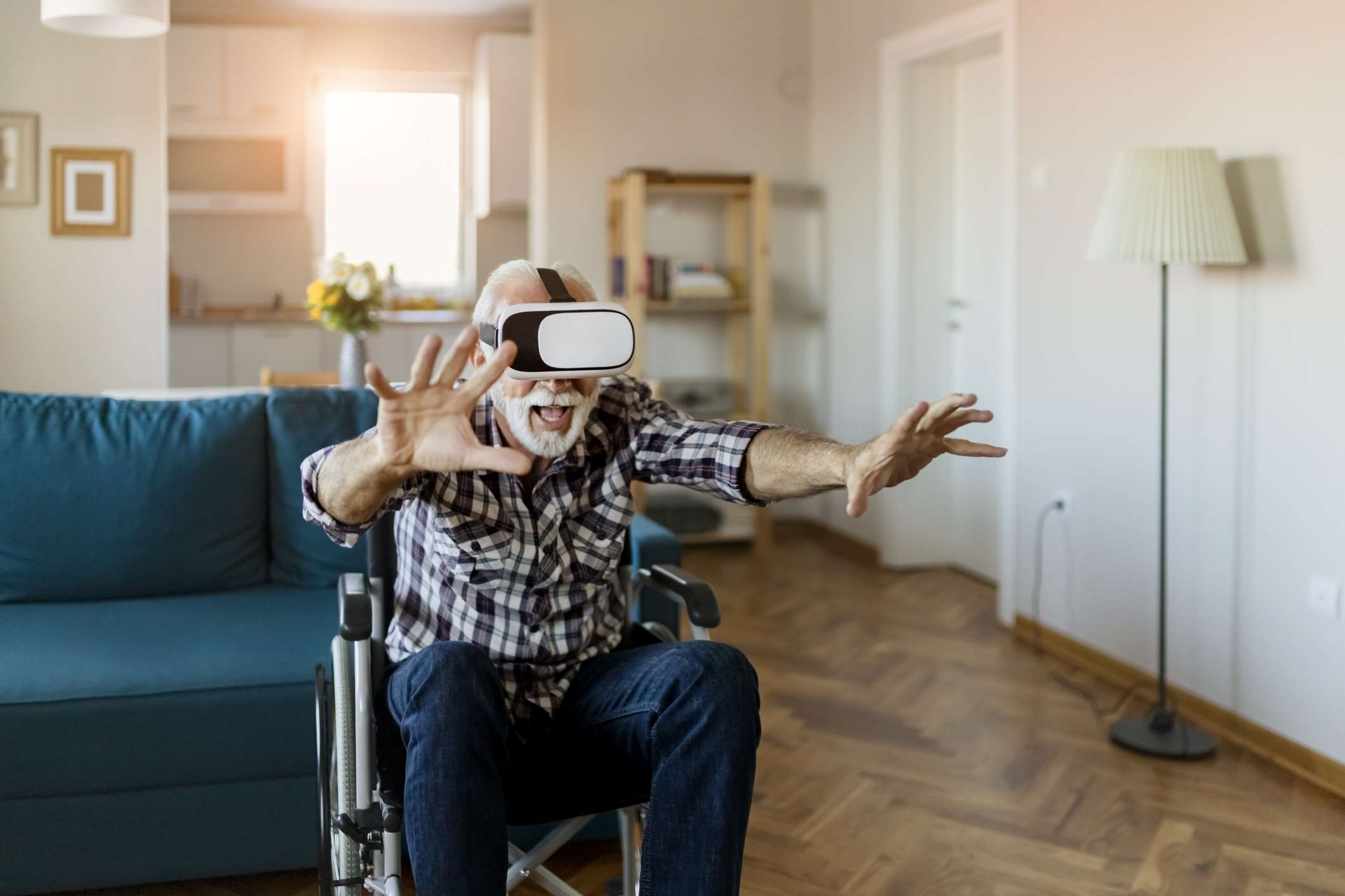 An elderly person in a wheelchair, using a VR headset alone.